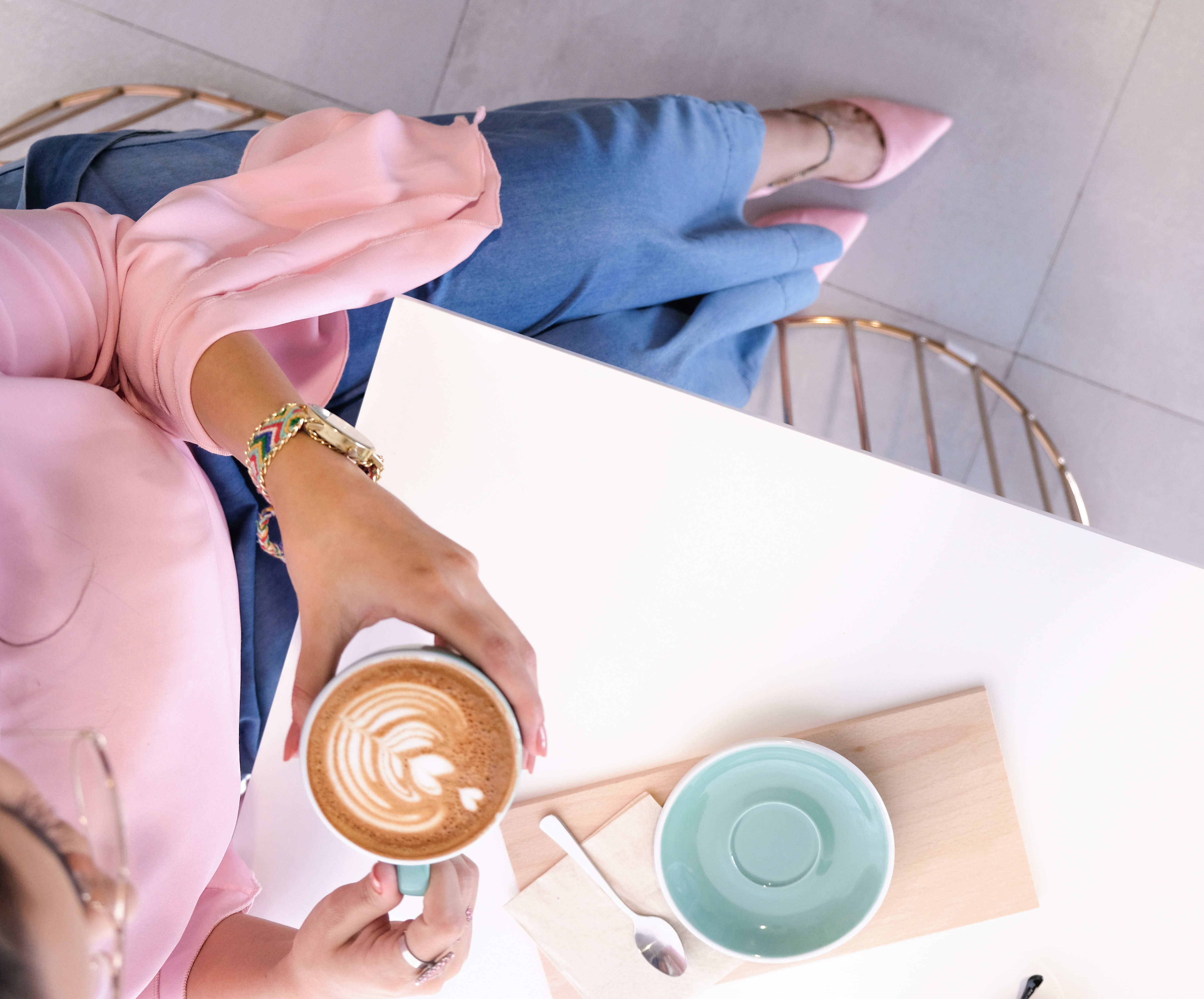 woman-holding-mug-with-coffee-sitting-at-desk-1260599